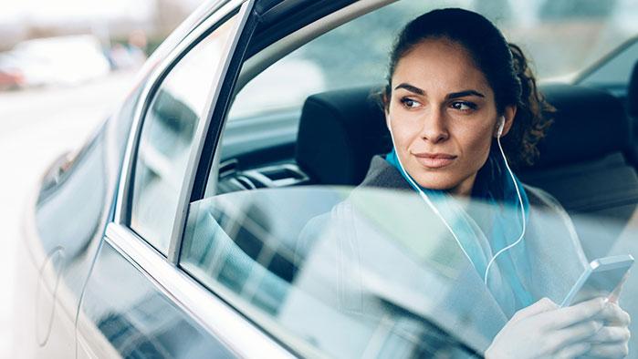 Frau im Businesslook sitzt im Fond eines Wagens und sieht aus dem Fenster, Smartphone in der Hand.