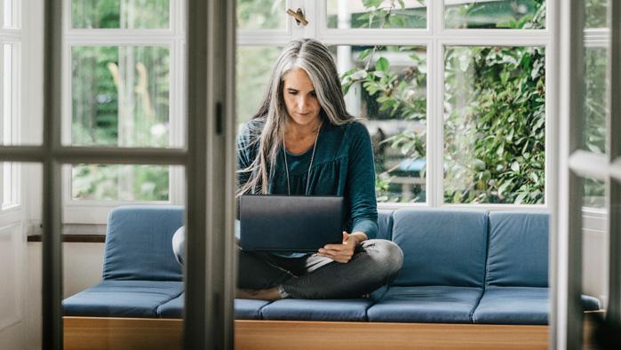 Angestellte arbeitet von zu Hause aus auf ihrem Laptop