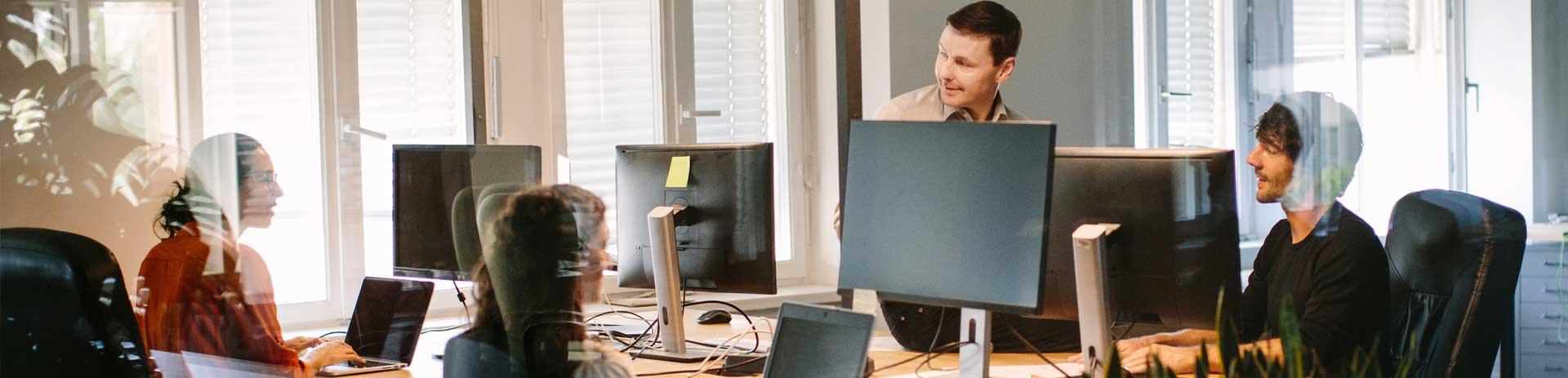 Mitarbeiter in Gespräch auf einem Vier-Personen-Arbeitsplatz