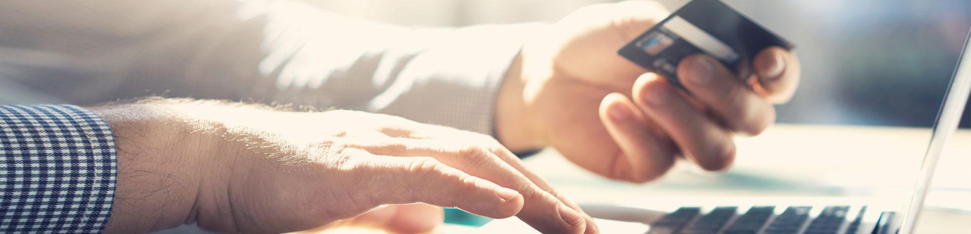 Hände halten Kreditkarte vor geöffnetem Notebook