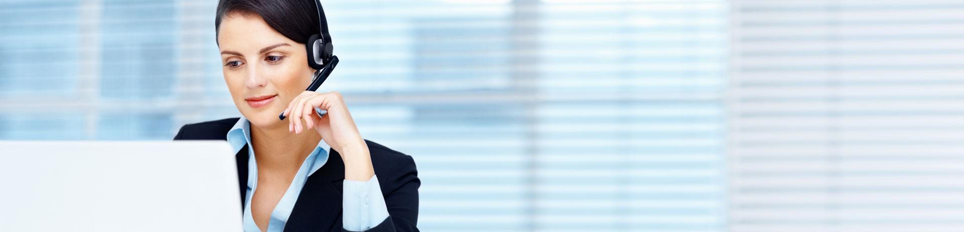 Businessfrau mit Headset telefoniert vor einem Notebook