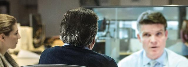 Zwei Personen kommunizieren mit einer Person über Videokonferenz