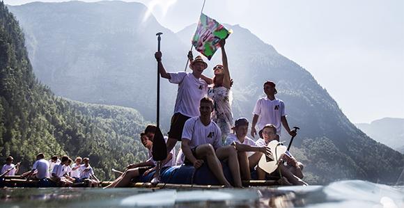 Lehrlinge sitzen auf einem selbst gemachten Boot und genießen die Fahrt auf einem See; Berge im Hintergrund