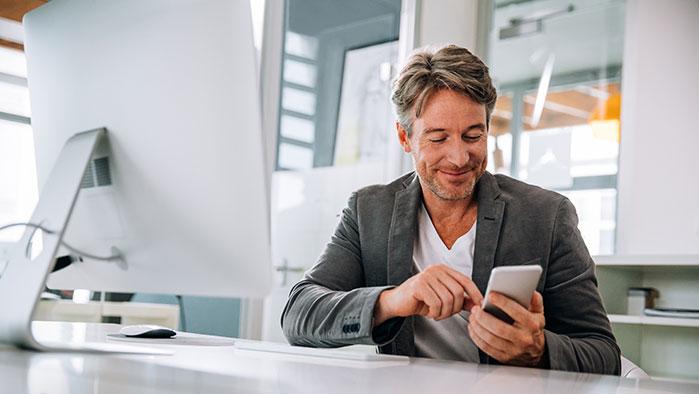 Mann im Office bedient gerade sein Smartphone