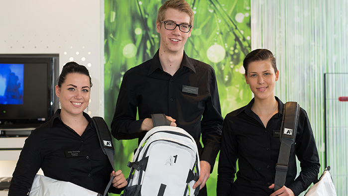 3 junge Mitarbeiter lächeln in die Kamera und halten dabei schwarz weiße A1 Rucksäcke in der Hand