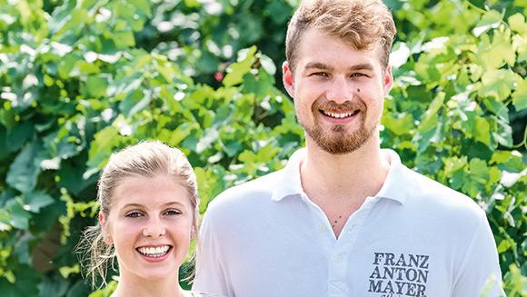 ein junges Pärchen steht vor einem grünen Baum; der junge Herr hat auf seinem T-Shirt das Logo des Weinguts
