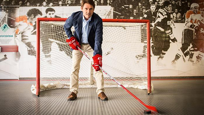 Person in Business-Kleidung steht in einem Eishockeytor mit Handschuhen und Schläger