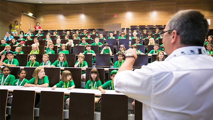 ein A1 Mitarbeiter steht in einem Hörsaal der Universität vor einer großen Gruppe Kinder, die alle ein grünes T-Shirt tragen und interessiert zuhören