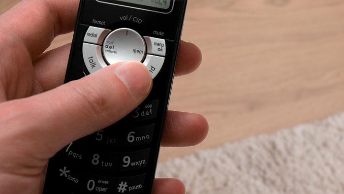 Hand, die ein Festnetz-Telefon bedient