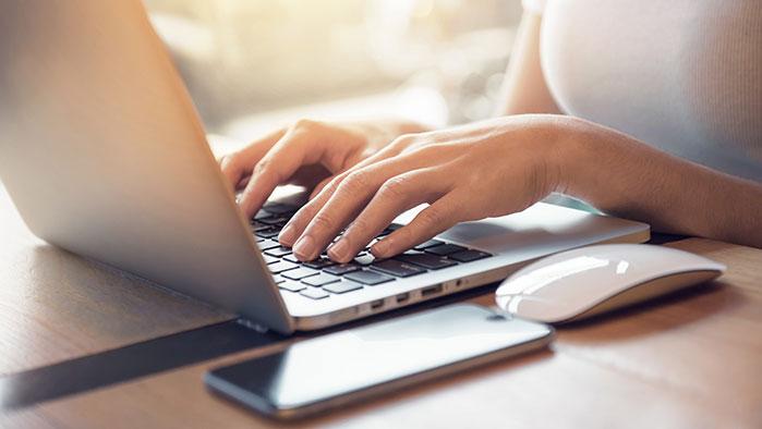 Hände einer Unternehmerin, die am Laptop arbeitet