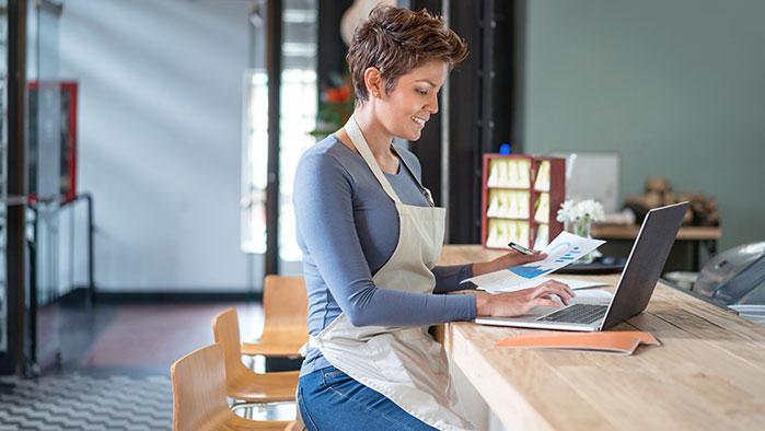 Unternehmerin, die am Laptop arbeitet und lächelt