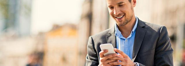 Mann auf der Straße bedient Smartphone