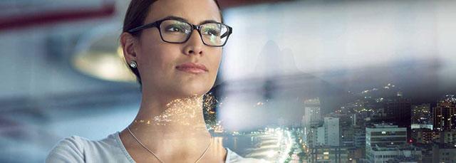 Frau mit Brille sieht durch Fenster Skyline einer Stadt