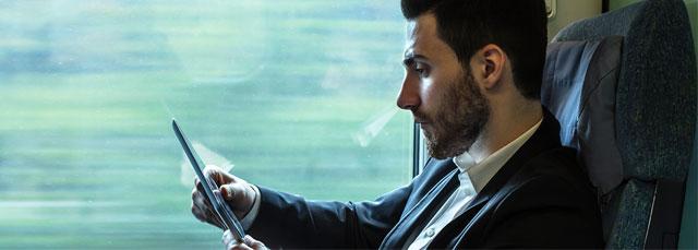 Mann sitzt im Zugsabteil mit Tablet