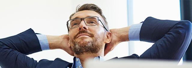 Business-Mann relaxed und lehnt sich am Sessel zurück