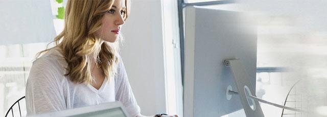Frau arbeitet am Schreibtisch und sieht in einen Bildschirm