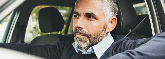 Mann mit grauem Bart sitzt im Auto bei offener Scheibe