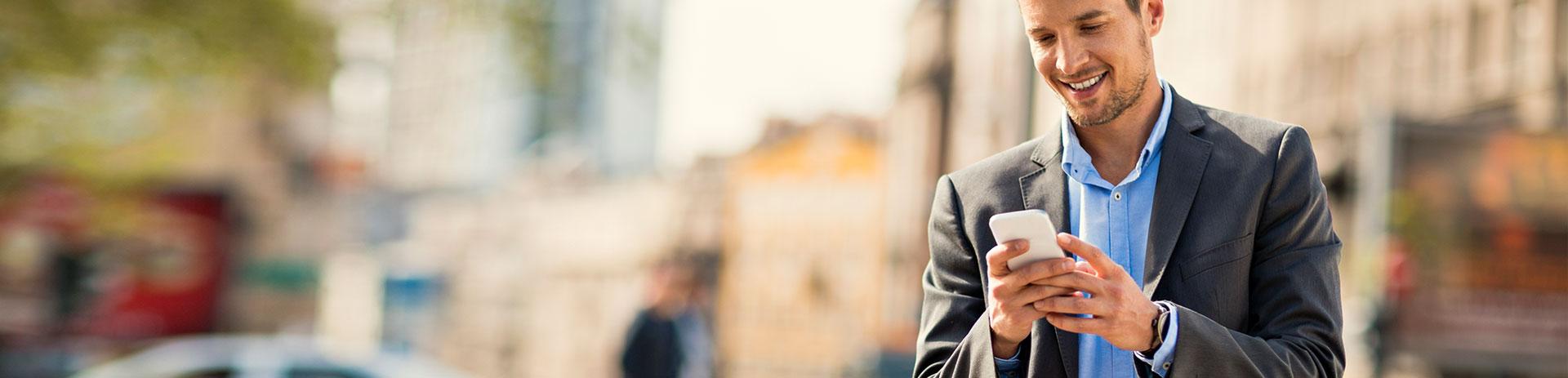 Mann im Sakko bedient Smartphone in der Stadt