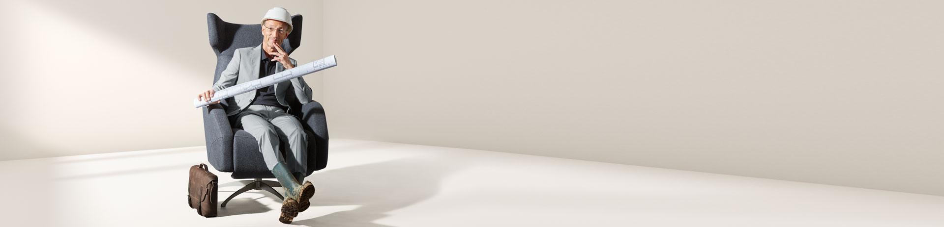 Architekt sitzt in Polstersessel mit Baustellenhelm und Stiefeln