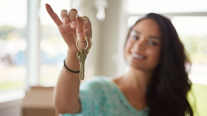 Junge Frau präsentiert Schlüssel nach Übergabe der neuen Wohnung