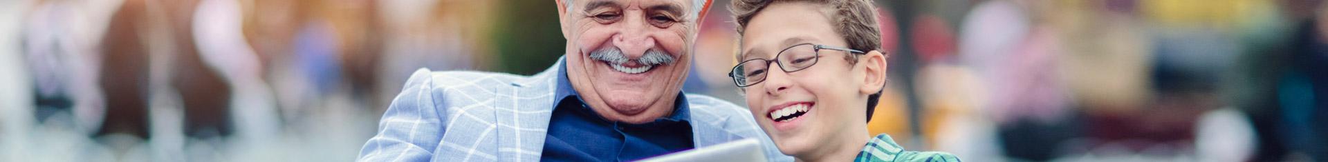 ein älterer Herr sitzt mit einem Kind lachend in einem Park; beide sehen dabei auf ein Tablet