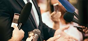 Bildausschnitt einer Pressekonferenz mit Mikrofonen und Handys in den Händen