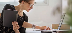Frau arbeitet sowohl auf Tablet als auch mit Notebook