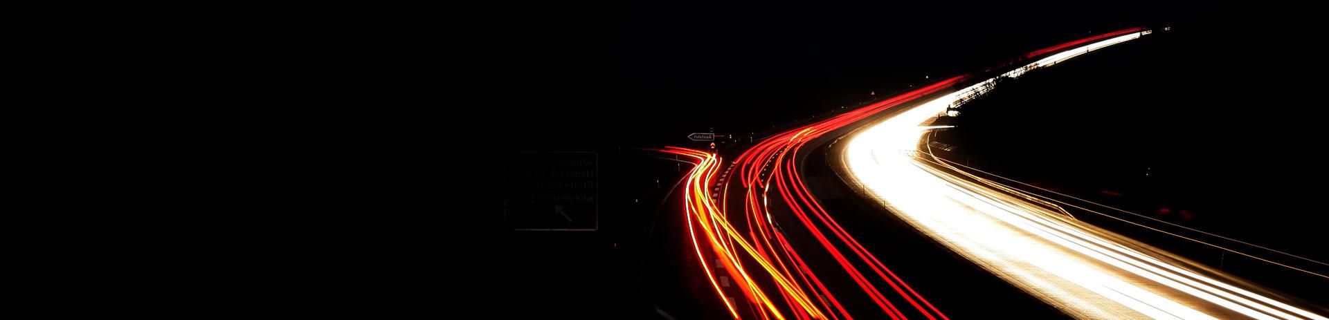 Autobahn in der Nacht mit weißen und roten Leuchtstreifen