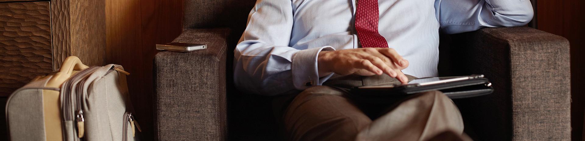 Businessman in Hotellobby auf Stoffsessel