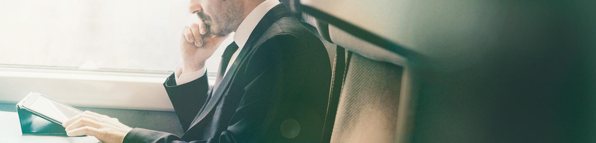 ein Mann im Businessoutfit sitzt in einem Zug und arbeitet auf seinem Tablet