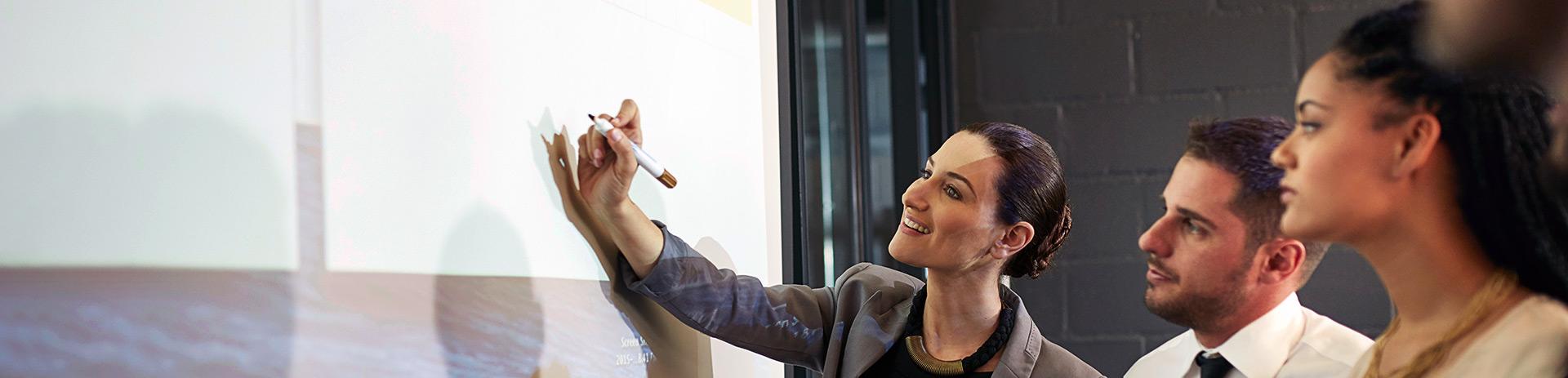 Eine Dame schreibt etwas auf ein Flipchart. Zwei Männer und eine Frau verfolgen ihre Schritte interessiert
