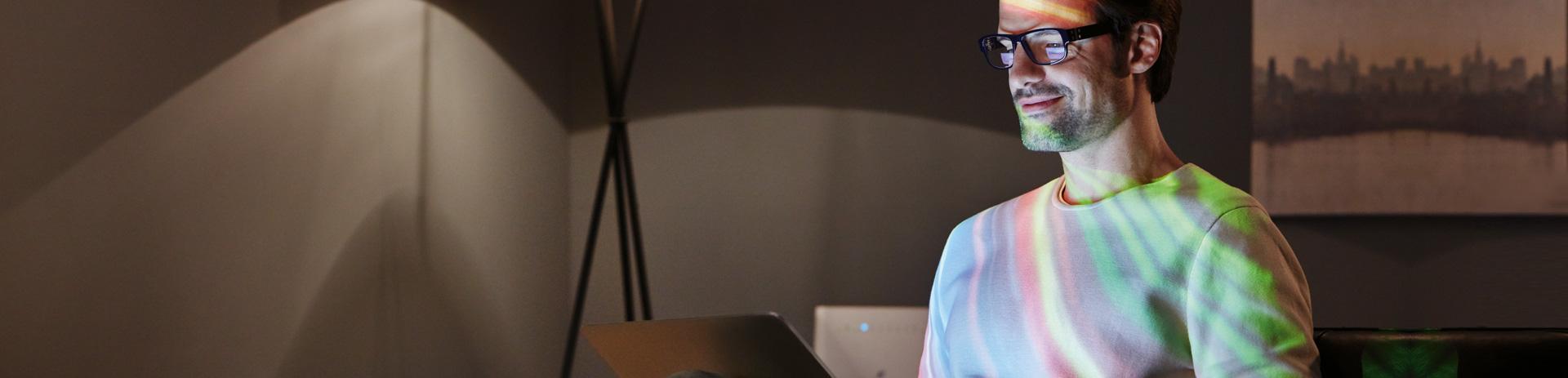 Mann mit Laptop und Lichtreflexen