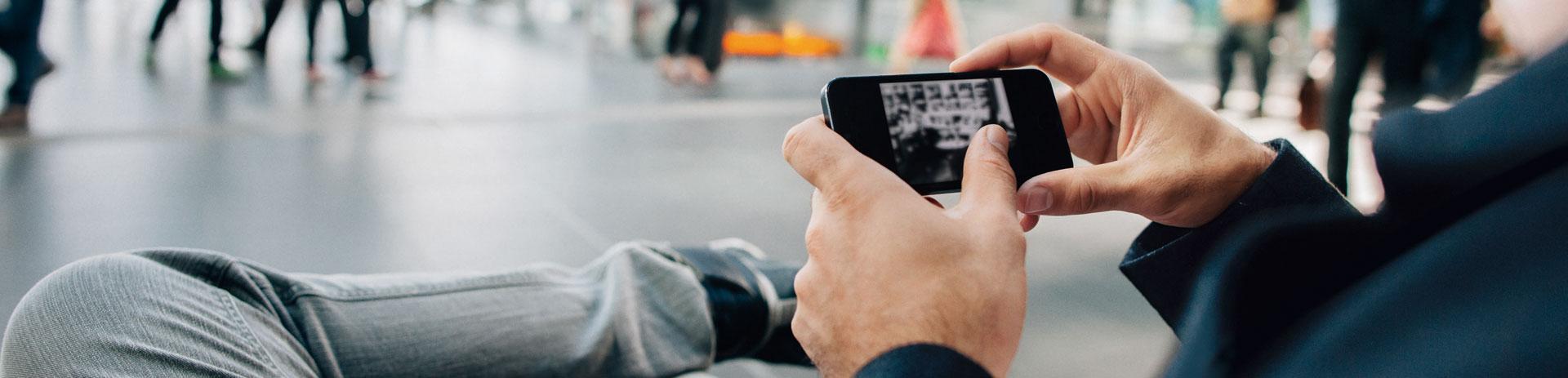 Mann in Ankunftshalle surft mit seinem Handy