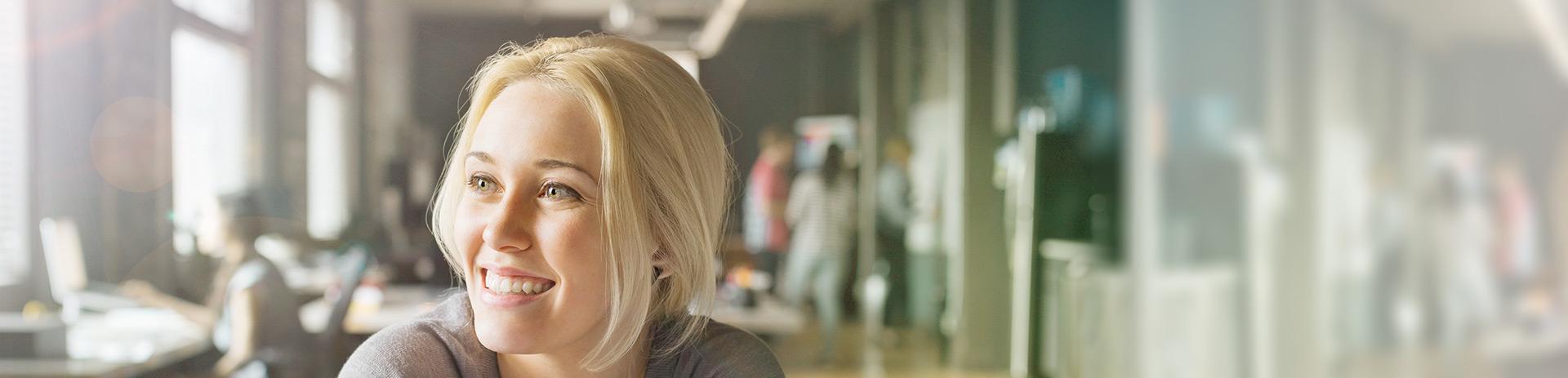 Lächelnde Geschäftsfrau mit Büro im Hintergrund
