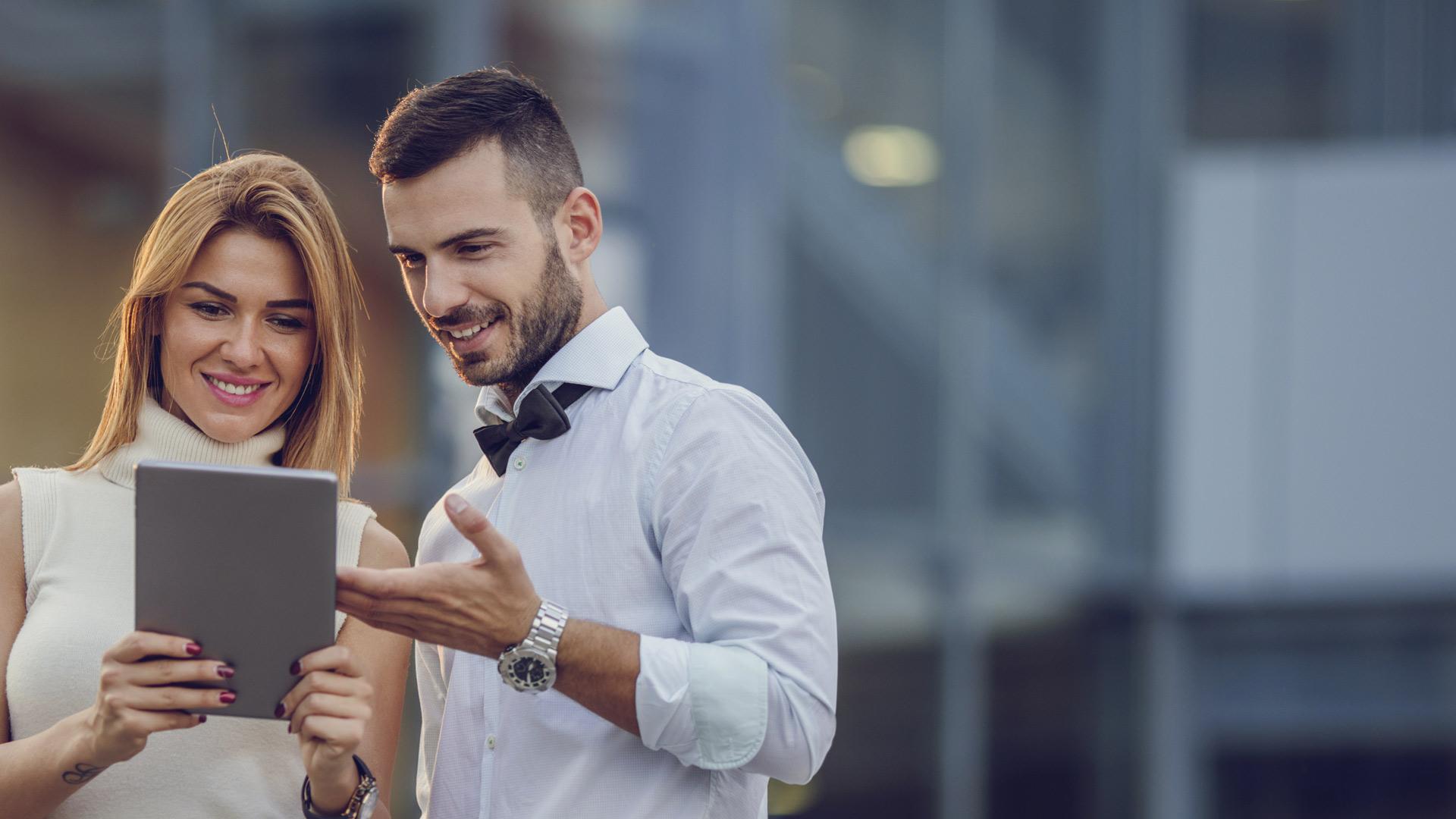 Mann zeigt Frau etwas auf einem Tablet