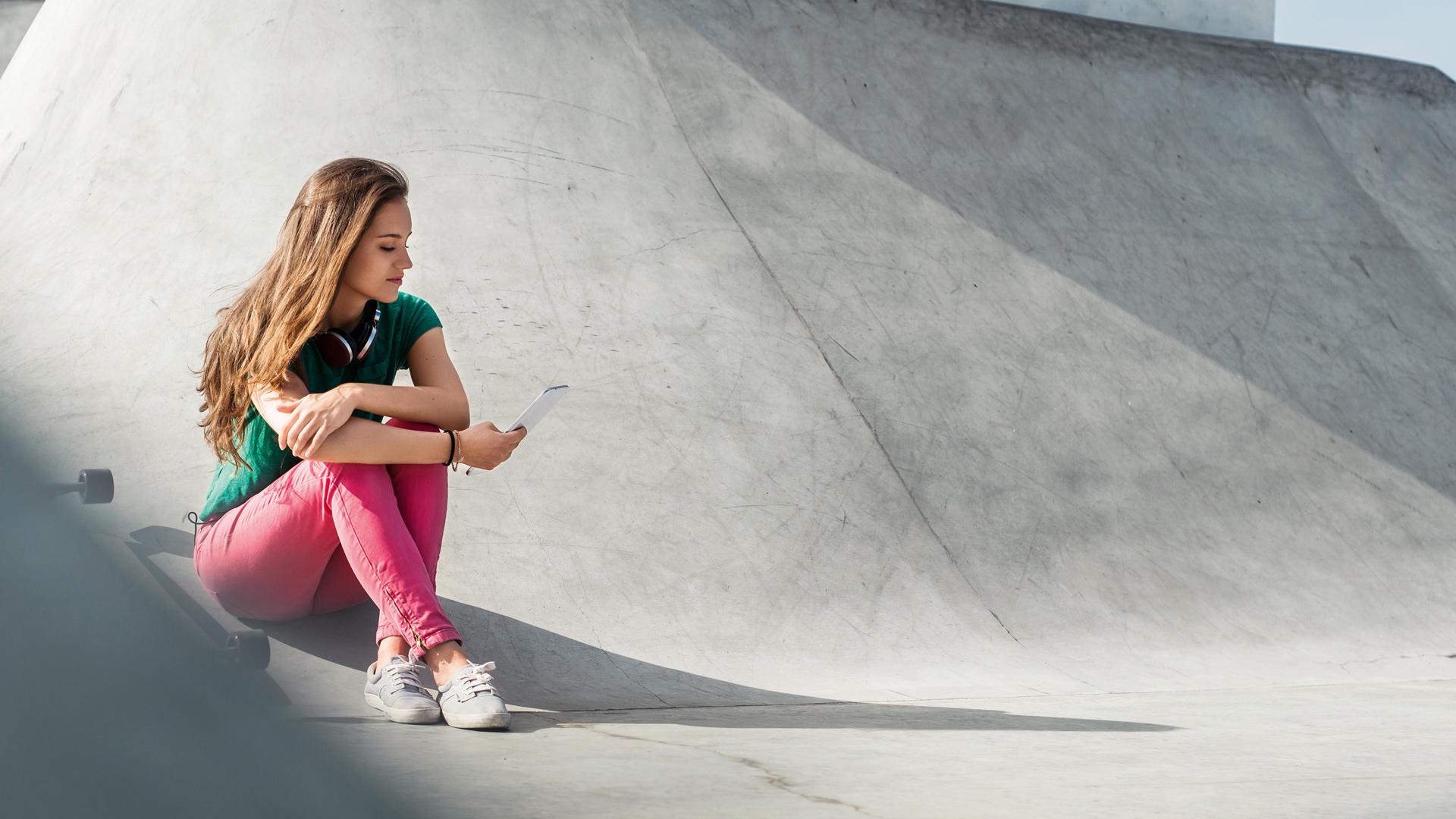 Junge Frau mit Smartphone im Skaterpark.
