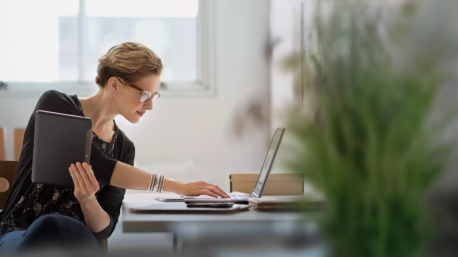 Frau mit Tablet und Notebook