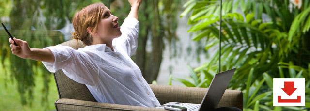 eine Frau sitzt auf einem bequemen Sessel, hat den Laptop auf dem Schoß und lehnt sich entspannt zurück; im Hintergrund sieht man viele Bäume und Sträucher