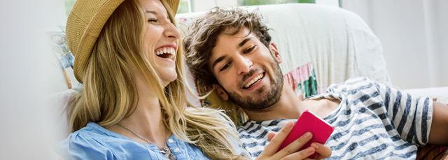 Lachende Frau mit Handy und lachender Mann