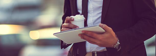 Geschäftsmann mit Tablet und Coffee-to-go-Becher