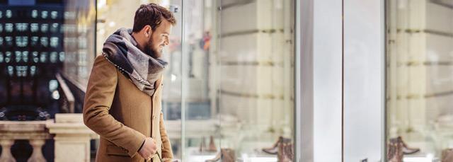 Ein Mann, der in ein Schaufenster mit Schuhen schaut.