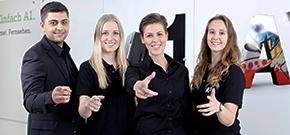 ein männlicher und drei weibliche Lehrlinge lächeln erfreut in die Kamera und machen dabei eine einladende Gesten