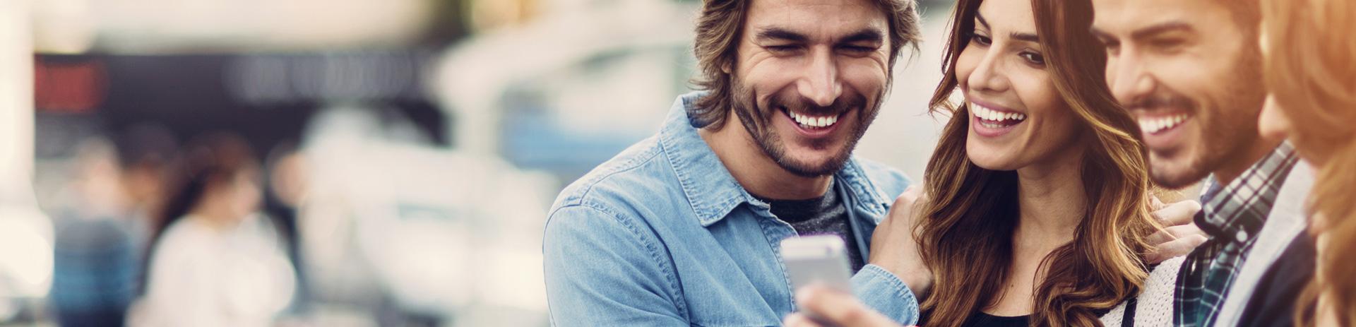 2 Frauen und 2 Männer, die lachen und auf ein Smartphone schauen