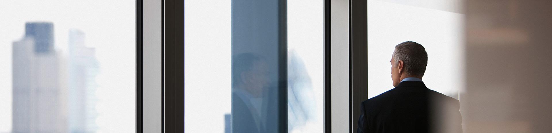 älterer Mann mit Blick aus Fenster