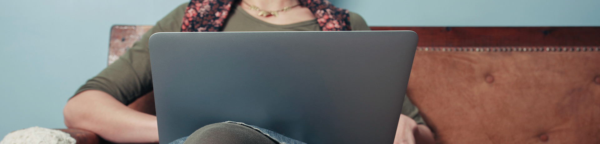 Frau mit Laptop auf roter Ledercouch