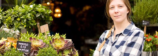 Frau steht vor Eingang zu Obst/Gemüsestand