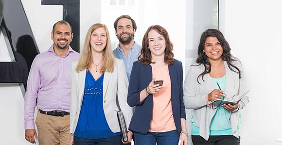 eine Gruppe aus 3 weiblichen und 2 männlichen Graduates steht lächelnd vor einem A1 Logo