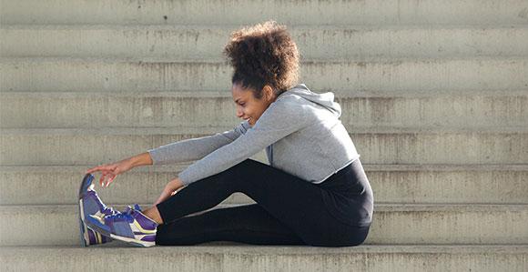 Eine Frau im Sportoutfit sitzt auf den Stufen und wärmt sich für das Training auf