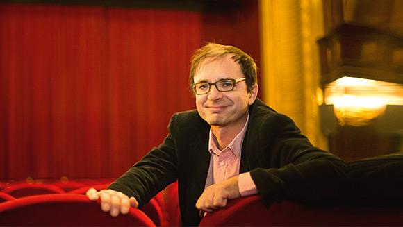 Mann im Anzug sitzt in einem Kinosaal mit roten Samtstühlen; im Hintergrund sieht man verschwommen einen roten Samtvorhang vor der Leinwand