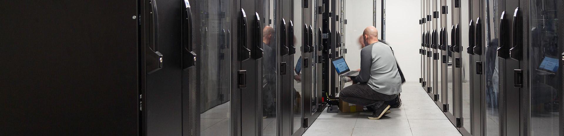 2 Techniker sitzen mit ihrem Laptop in einem großen Serverraum